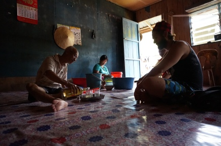The chief Iban of the longhouse pouring us some Tuok, which is a rice wine.